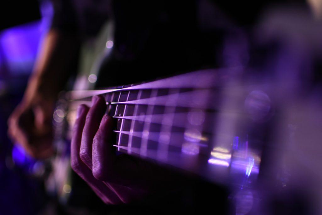 エレキベースを演奏している人の手元をアップで写した画像
